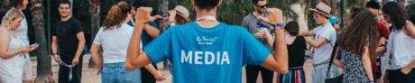 """Poika seisoo selin kameraan ja osoittaa paitaa, jossa lukee """"Media"""". Taustalla muita nuoria."""